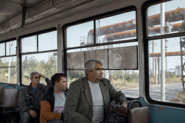 Arbeiders zitten in de tram onderweg naar hun werk in het industriële gebied in Perm. Beeld Emile Ducke