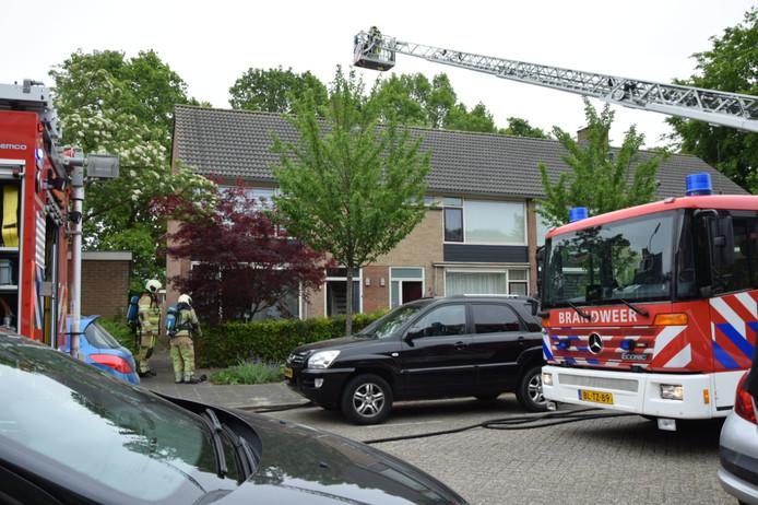 De brandweer gebruikt de ladderwagen om de zolderbrand te bestrijden.