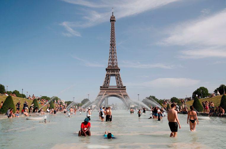 Mensen zoeken verkoeling in de fonteinen aan Trocadero bij de Eiffeltoren.