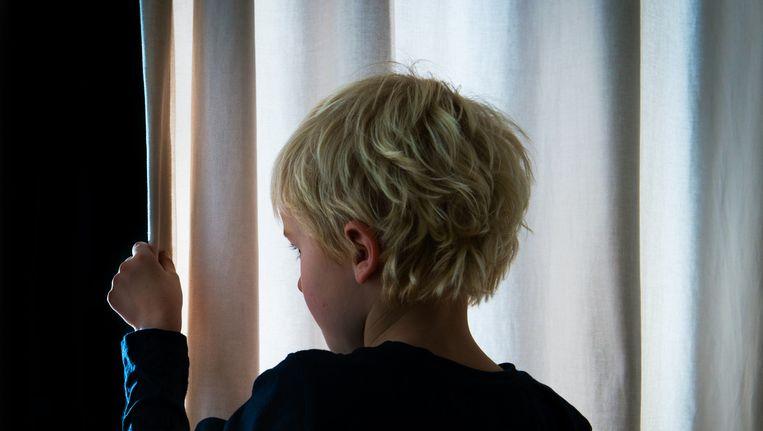 Een jongen in pyjama gluurt door de gordijnen. Beeld anp