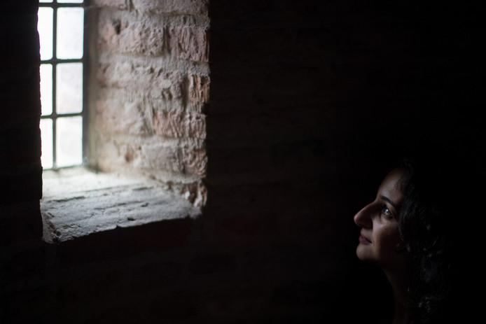 Armita Taheri, Statenlid voor het Forum voor Democratie in Gelderland, kijkt uit een raam van de Sabelspoort naast het provinciehuis in Arnhem.