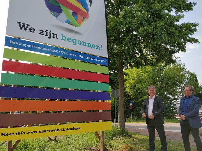 Wethouders Peter Smit (links) en Jan de Laat onthullen het bouwbord op sportpark Den Donk.