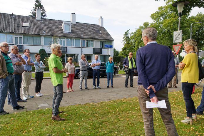 Anne Regts van het IVN (in gele shirt) geeft de bewoners van de Helmondse Boerhaavelaan tijdens een rondleiding uitleg over welke bomen verdwijnen en wat ervoor terug komt.