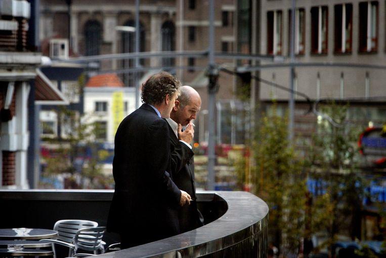 Politici Thom de Graaf en Jan Marijnissen roken op het balkon van de Tweede Kamer een sigaretje. Beeld ANP