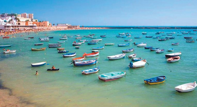 Zonnebaden doe je in Cadiz met zicht op een burcht, vissersbootjes en de stad op het stadsstrand La Caleta.