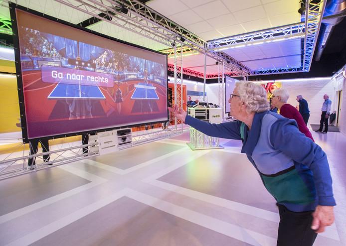 Een man staat op het punt om te beginnen aan een virtueel potje tafeltennis in Fun-ie-Fit in het Meester Siebelinkhuis, gedurende het project Game, Eet & Match. Monique Schuchart wil een variant daarvan aanbieden aan dementerenden.