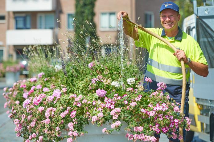 Harm van Aalst geeft als medewerker buitendienst de bloemen in Uden water.