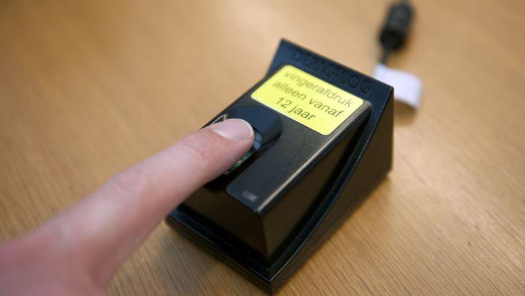 Een man geeft zijn vingerafdruk af voor een biometrisch paspoort. Beeld anp