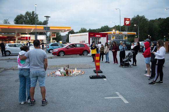 Mensen plaatsen kaarsjes en leggen bloemen aan het tankstation in Botkyrka, ten zuiden van Stockholm.