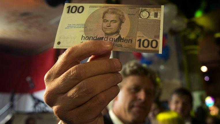 Ton van Kesteren, de noordelijke kandidaat voor de PVV, toont een vals 100 gulden biljet met een afbeelding van PVV-leider Geert Wilders in een cafe in Den Haag. Beeld anp