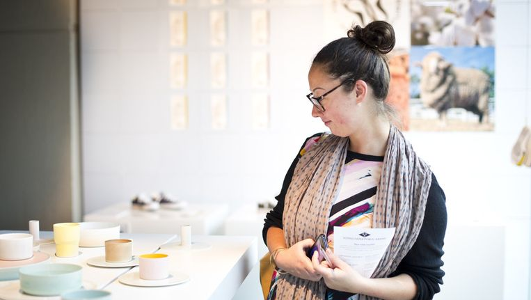 Een bezoekster bekijkt een servies van ontwerpersduo Scholten & Baijings tijdens de Dutch Design Awards expositie in het Stadhuis in Eindhoven, 2012. Beeld null
