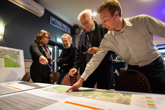 Tijdens de informatiebijeenkomst over de dijkverhogingen in Terheijden buigen inwoners zich over de voorgestelde plannen.
