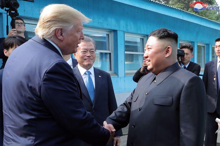 Trump en Kim Jong-un schudden elkaar de hand, de Zuid-Koreaanse president Moon Jae-in kijkt goedkeurend toe.