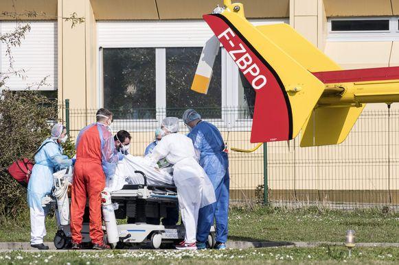 Een coronapatiënt wordt vanuit het ziekenhuis in Mulhouse een brancard naar een medische helikopter gebracht.