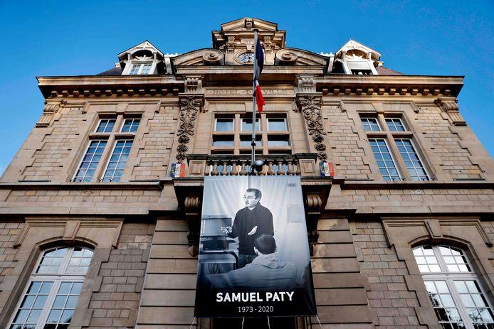 Aan het gemeentehuis van Conflans-Sainte-Honorine hangt een groot spandoek, met daarop de afbeelding van Samuel Paty.