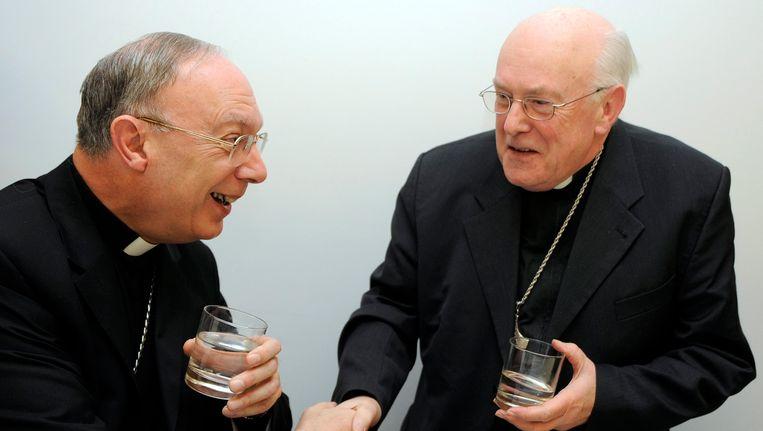 Aartsbisschop Andé-Joseph Léonard (l.) schudt kardinaal Godfried Danneels (r.) de hand.