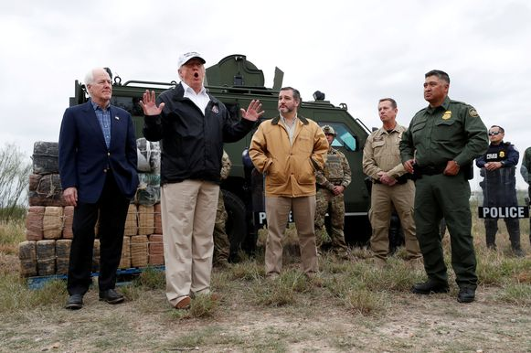 President Donald Trump aan de zuidelijke grens in Texas samen met de Republikeinse senatoren John Cornyn (links) en Ted Cruz uit Texas en enkele Amerikaanse grenspolitieagenten.