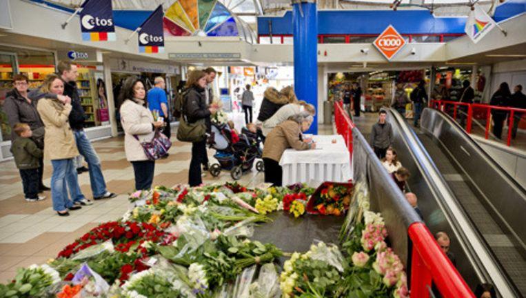 Bezoekers tekenen dinsdag een condoleanceregister in winkelcentrum De Ridderhof in Alphen aan den Rijn, waar afgelopen zaterdag een man zes mensen dood schoot. Het winkelcentrum is dinsdagochtend weer open gegaan voor het publiek. © anp Beeld