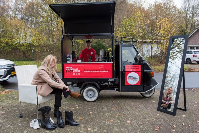 Evelien van Breemen bij de 'mobiele mini-schoenenzaak' van Bata op de stoep voor haar huis. Op de achtergrond 'Shoefeur' Giel Wijnands.