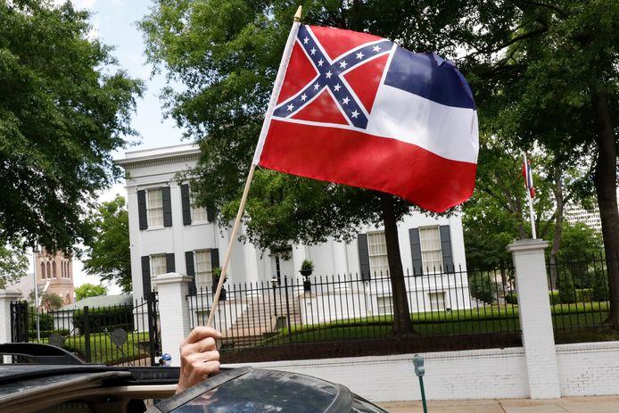 Een automobilist zwaait met een staatsvlag van Mississippi voor het huis van de gouverneur in Jackson tijdens een betoging om de vanwege de coronacrisis grotendeels stilgelegde economie in de staat weer te heropenen.