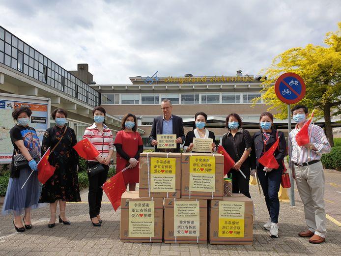 De Chinese delegatie poseert voor het Slingeland Ziekenhuis, met XinXin Hu (derde van links). Hans Hageman van het Slingeland Ziekenhuis (midden) wordt geflankeerd door Tan (rechts) en Yang (links), beiden leden van de Stichting LFCON. Uiterst links Fu uit Terborg die samen met Hu het initiatief nam voor de actie.