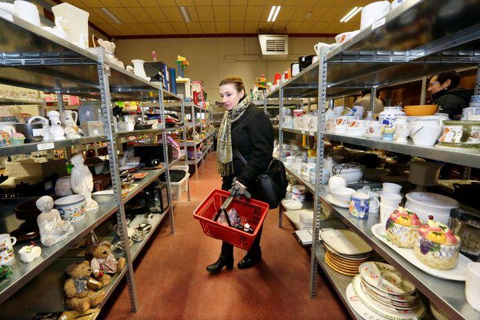 Een klant zoekt tussen de tweedehandsspullen in Kringloopwinkel Vindingrijk aan de Riethil in Breda. Binnenkort ook mogelijk in de binnenstad.