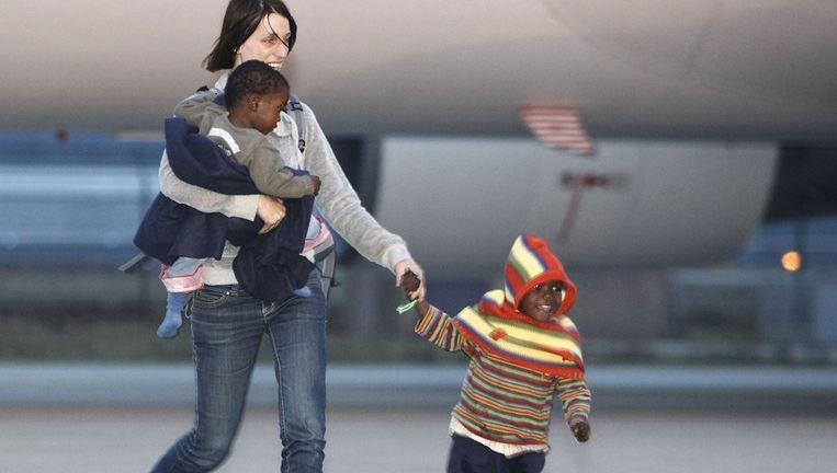 Een nieuwe moeder komt aan op luchthaven Eindhoven met haar adoptiekinderen uit Haiti, januari 2010. Beeld ANP