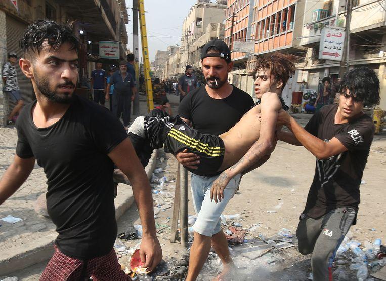 Jonge mannen dragen een kameraad weg die gewond is geraakt bij schermutselingen met de oproerpolitie tijdens protesten in Bagdad. Beeld AFP