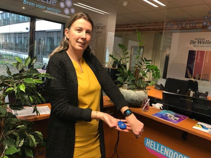 Jolanda van Rooyen van Stichting De Welle met de nieuwe mobiele personenalarmering: met één druk op de knop kan iemand die in nood is al in contact komen met bekenden.