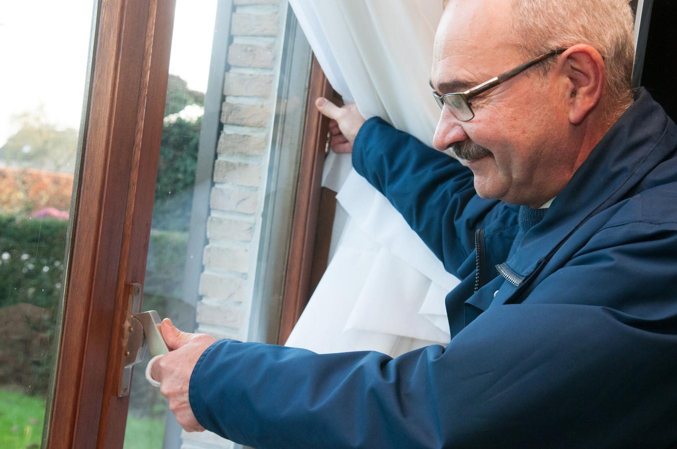 """Hoofdinspecteur Guido Moerman op bezoek bij Peter De Smeyter in Mullem. """"Dit raam is een makkie voor inbrekers: ze boren een gaatje en duwen de hendel weg."""""""