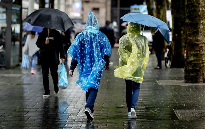 Mensen trotseren de regen in het centrum van Amsterdam.