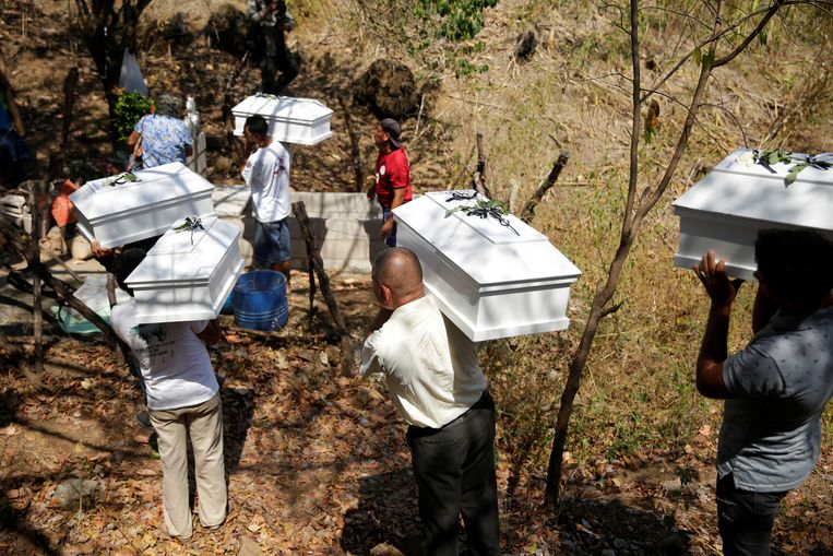 Inwoners van El Calabozo in El Salvador dragen zes lijkkisten met daarin de stoffelijke overschotten van mensen die in 1982 tijdens de burgeroorlog omkwamen bij een massale executie door het leger van El Salvador. Daarbij werden 200 burgers gedood. Zes van hen kregen vrijdag de kerkelijke zegen en een waardige begrafenis. Beeld EPA