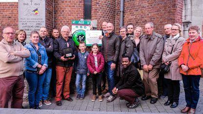 Kerkfabriek en sponsors hangen defibrillator aan kerkmuur