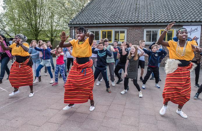 Kinderen van de Adalbertschool in Mook dansen mee met de Keniaanse dansgroep Tarumbeta. Op dezelfde speelplaats rennen ze later rondjes voor het goede doel.