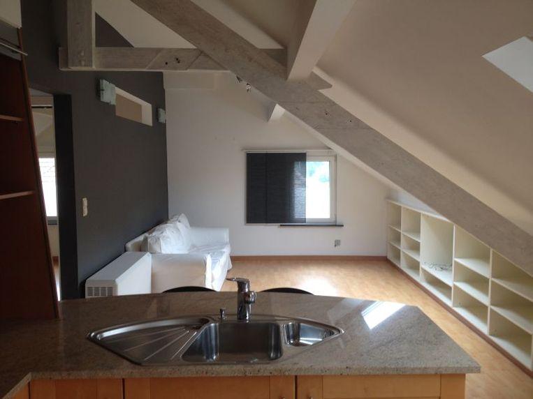 De woonkamer is afgewerkt met lichte vloeren met houtstructuur, witte maatkasten en licht geverfde open balken voor een luchtig effect.