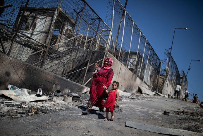 Een moeder met twee kinderen in het uitgebrande vluchtelingenkamp van Moria