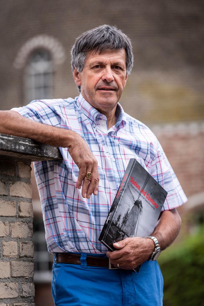 Cor Vervoort voor de molen in Eerde met zijn boek in de hand vol ooggetuigenverslagen