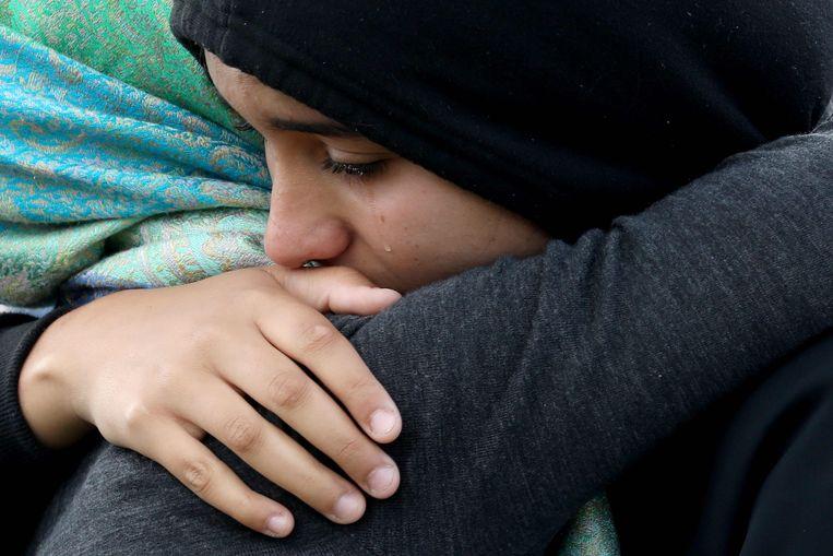 Meisjes huilen en omhelzen elkaar tijdens de ceremonie.