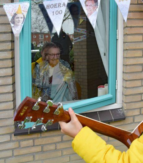 Zingen en dansen in de groenstrook voor oma Anna die honderd kaarsjes uitblaast
