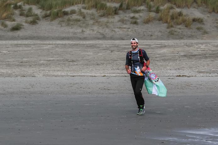 Steven Schless uit Rotterdam liep het driedaagse traject Vlissingen-Rotterdam gelijk op met de sloeproeiers van Dutch Marines Rowing Challenge. Hier loopt hij het strand van Westenschouwen op aan het einde van de eerste dag.