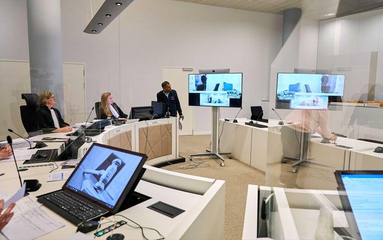 Een zitting in de 'anderhalvemeterrechtbank' van Den Haag tijdens de coronacrisis. Tussen de rechters zijn plexiglas schermen geplaatst. De verdachten worden via een videoverbinding gehoord. Beeld ANP
