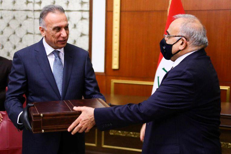 De nieuwe premier van Irak, Mustafa al-Kadhimi (links), krijgt de macht overgedragen van voormalig premier Adil Abdul Mahdi.  Beeld Reuters