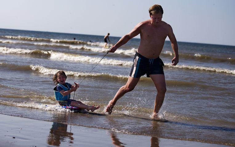 Een vader trekt zijn zoon voort op een bodyboard tijdens een prachtige dag op het strand van Hoek van Holland. Beeld ANP