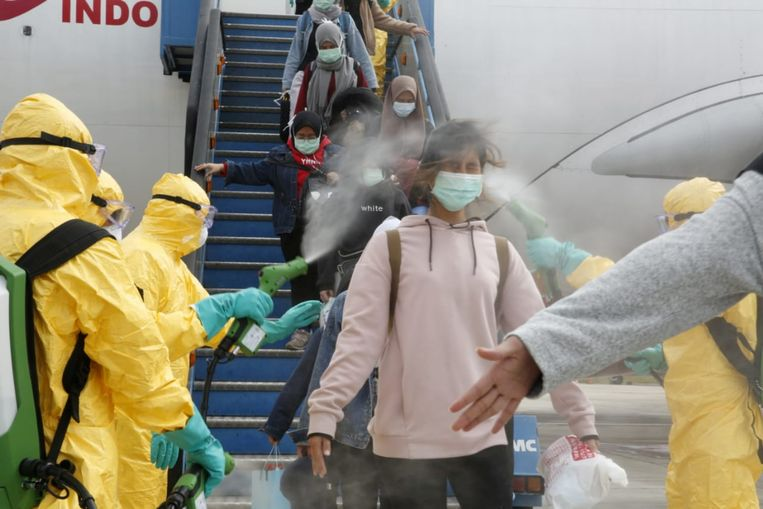 In het Indonesische Batam worden passagiers van een vlucht uit het Chinese Wuhan met een desinfectiemiddel besproeid, voordat ze naar een legerbasis worden gebracht waar ze veertien dagen  in quarantaine moeten. Beeld Reuters