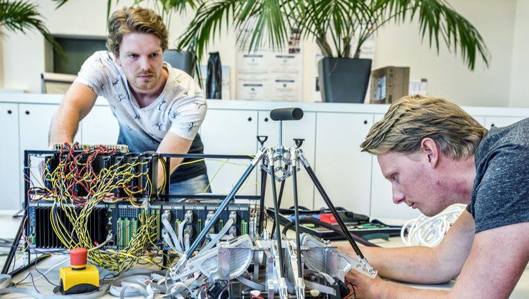Medewerkers van HIT sleutelen aan een afstandsbediening voor robots. HIT is een van de twintig bedrijven in het nieuwe RoboValley in Delft. Beeld raymond rutting