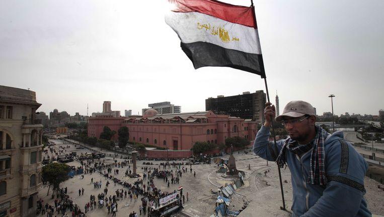 Een demonstrant met een Egyptische vlag op het Tahrirplein in Caïro. Beeld ap