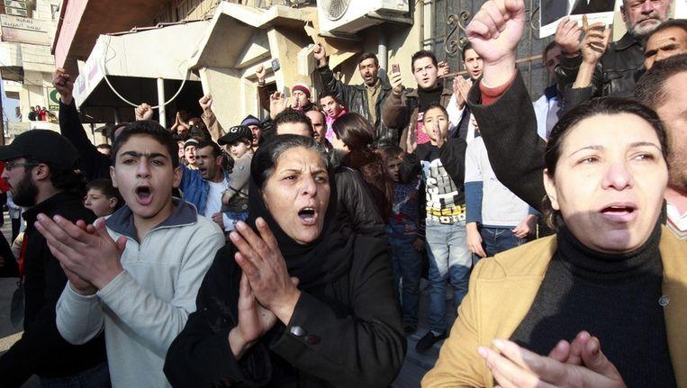 Mensen schreeuwen pro-regeringsleuzen tijdens een door de regering georganiseerde trip voor de pers. Beeld epa