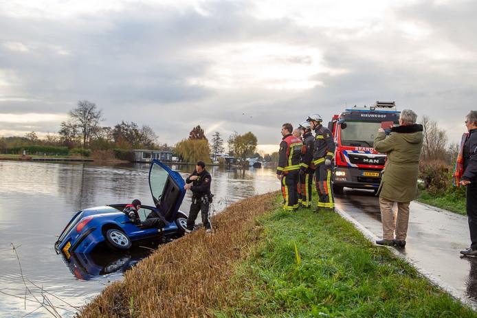 Brandweerlieden onderzoeken de auto nadat deze van de weg is gegleden en in het water is beland.