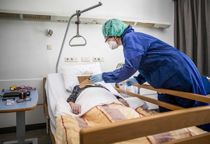 Een zorgmedewerker laat een familiefoto zien aan een coronapatient op een speciale cohort-afdeling in het Amphia ziekenhuis.