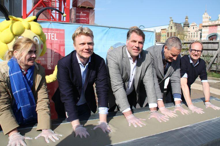 Toerismeschepen Cindy Verbrugge, Plopsa-directeur Steve Van den Kerkhof, burgemeester Bram Degrieck, Gert Verhulst en minister Ben Weyts drukken hun handen in het natte cement.